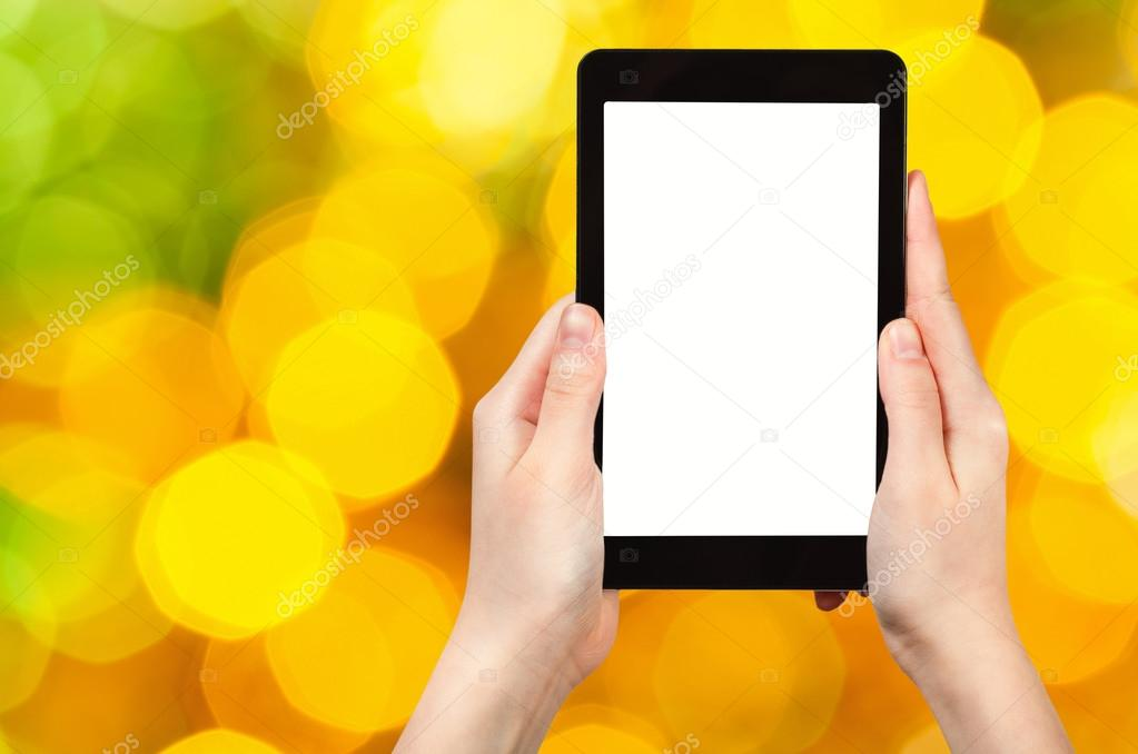hand with tablet pc on yellow and green background