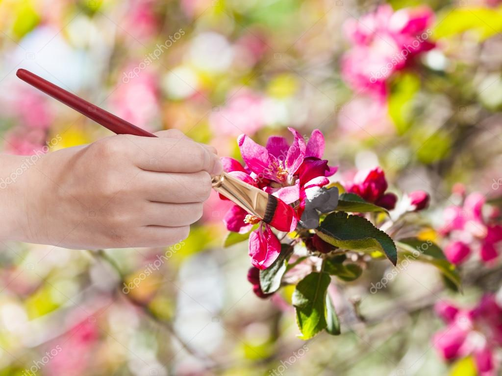 paintbrush paints red flowers on apple tree