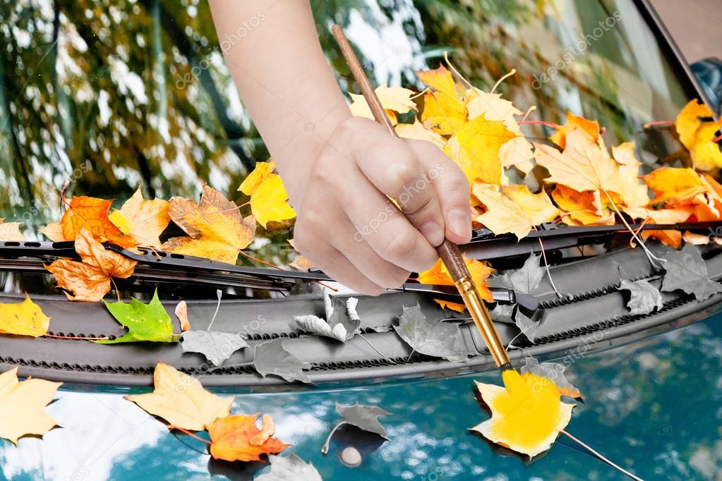 paintbrush paints yellow leaves on green car