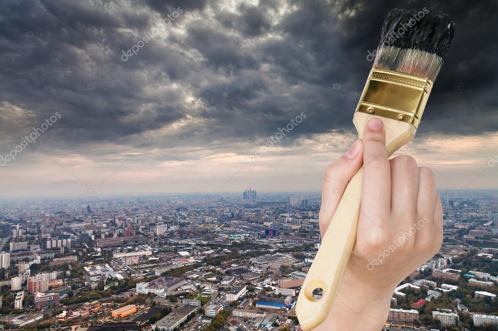 paintbrush paints storm clouds over dark city