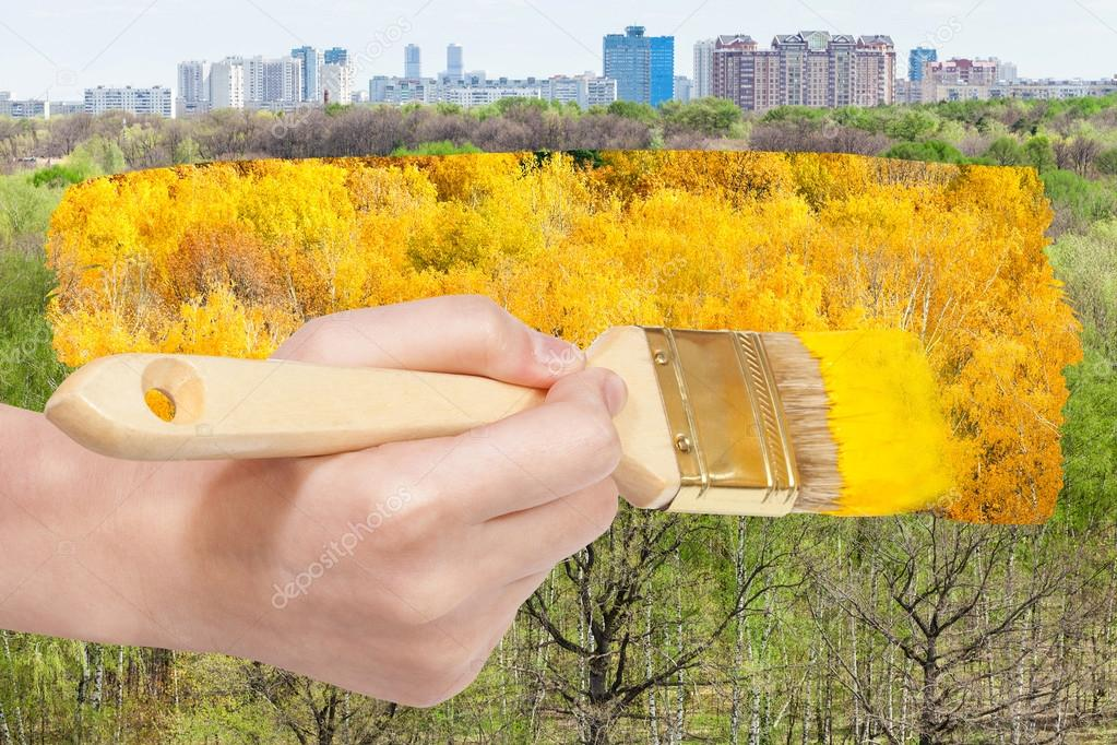 brush paints yellow foliage on green summer trees