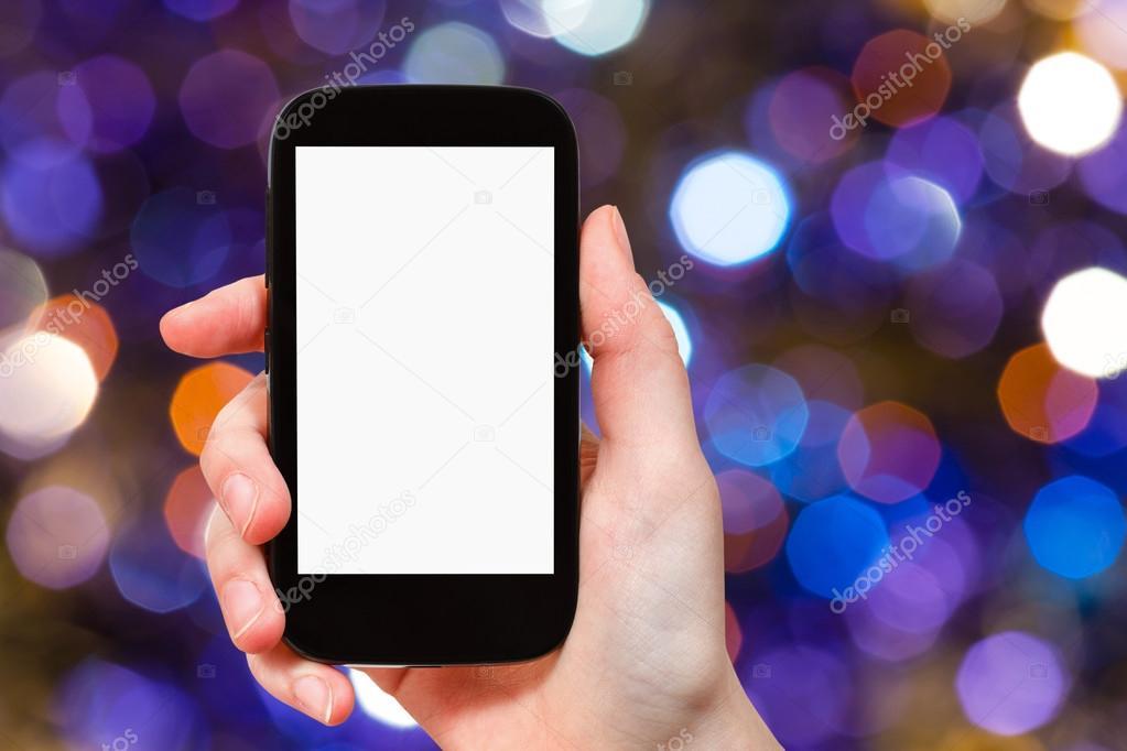 hand with smartphone on dark violet background