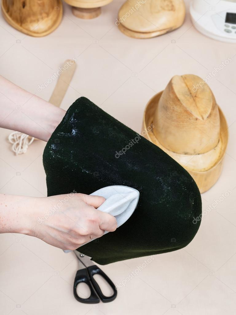 Hatter gluing a felt hood for shaping on hat-block — Stock Photo