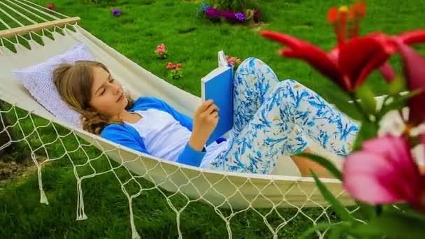 Dívka s knihou v houpací síti na zahradě