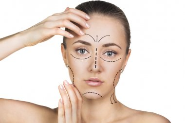 Beautician drawing perforation lines on woman face