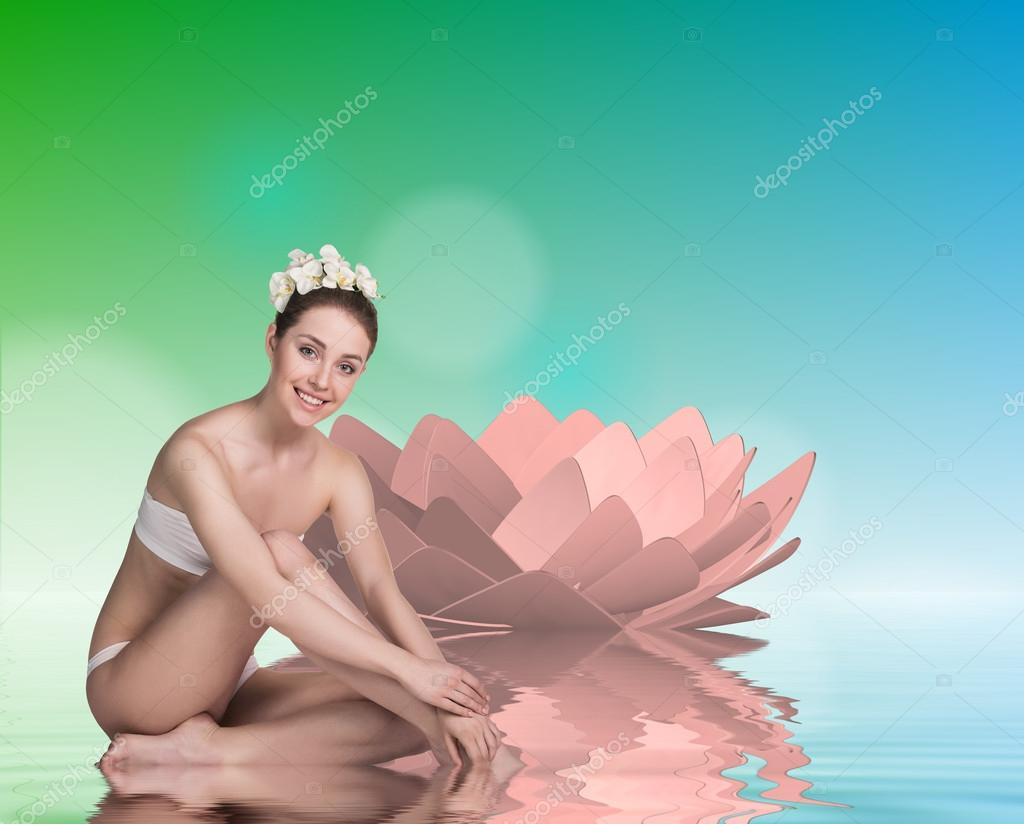 Young woman with lotus and stones on the water