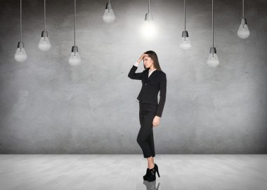 Business woman in room with hanging bulbs