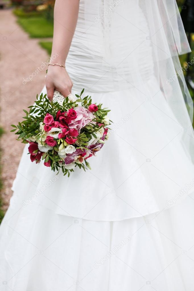 Bride holds wedding bouquet of flowers