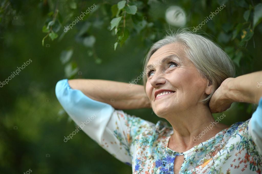 senior woman in summer park stock photo aletia 78523180