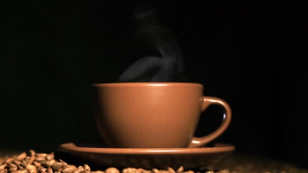 Cup of hot coffee, grains with steam   in orange tone. Black background