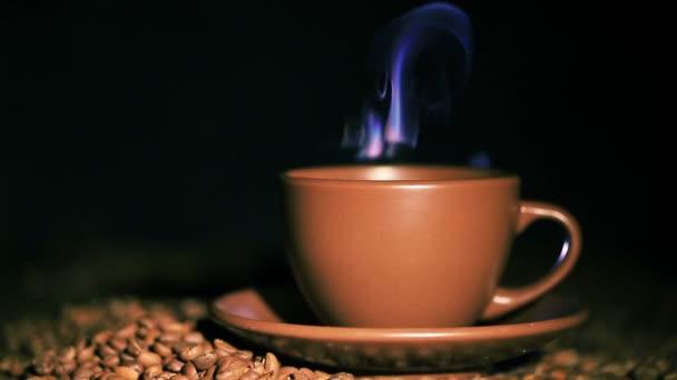 Šálek horké kávy, zrna s párou v oranžový tón. Pomalý parní