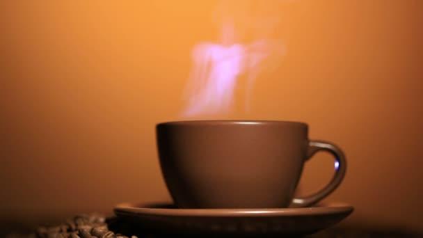Hnědé pohár s horkým nápojem a kávy, parní, oranžové pozadí