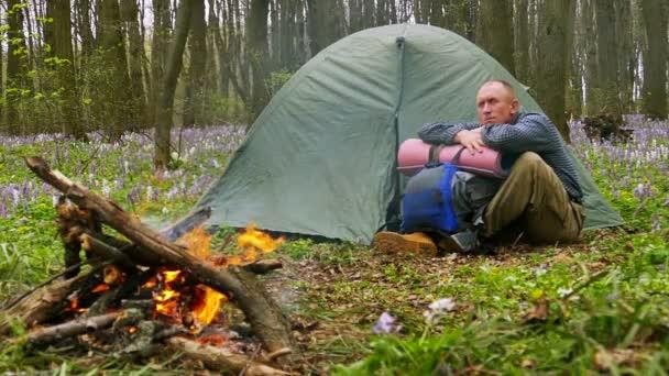 Lassítás 100 FPS-en. Felnőtt szomorú ember közel tábortűz és sátor gondol valamit.