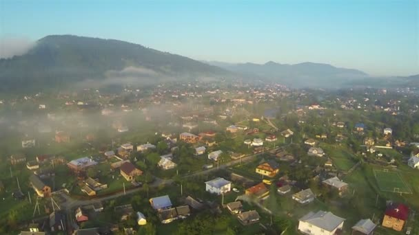 Village, mountains, small river and morning fog in  . Aerial shot   landscape