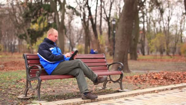 Adult man working on a tablet  in  park