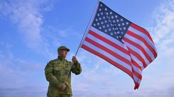 Soldier holds  American flag against blue sky and clouds. Slow motion scene
