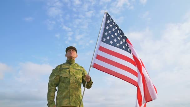 Soldier salute with  American flag against    blue sky. Slow motion scene