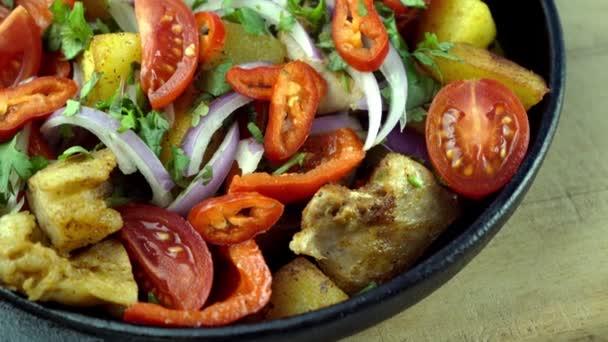 Rajčata, červená paprika, cibule, brambory a maso na pánvi. Zeleninové dušené maso. Vepřové ojakhuri se zeleninou. Gruzínská kuchyně. Nabídka domů.