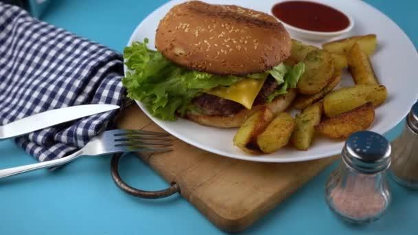 Hamburgerové menu s venkovskými brambory. Domácí nedokonalý burger s bramborami a salátem na talíři. Jídlo na stole v bílém talíři na dřevěné desce. Grilovaná buchta.