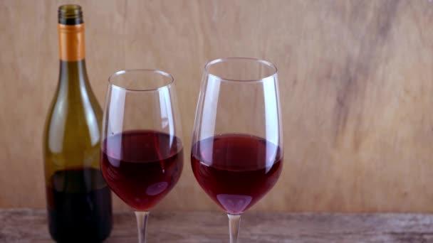 Dvě sklenky červeného vína. Alkoholický nápoj ve sklenici. Láhev vína. Dřevěné pozadí.