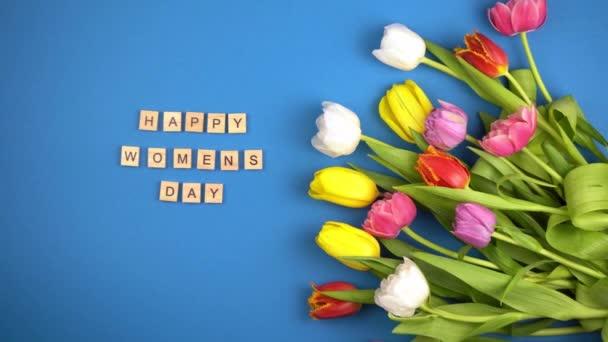 Mnohobarevné tulipány na pozadí bue horní pohled. Květiny Tulipán. Jarní prázdniny. Květinová kytice. Žluté, bílé, růžové, fialové pupeny. Šťastný dámský sms. Dřevěná písmena