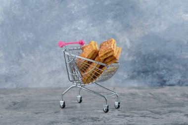 A small pink cart of tasty cookies placed on a marble background. High quality photo