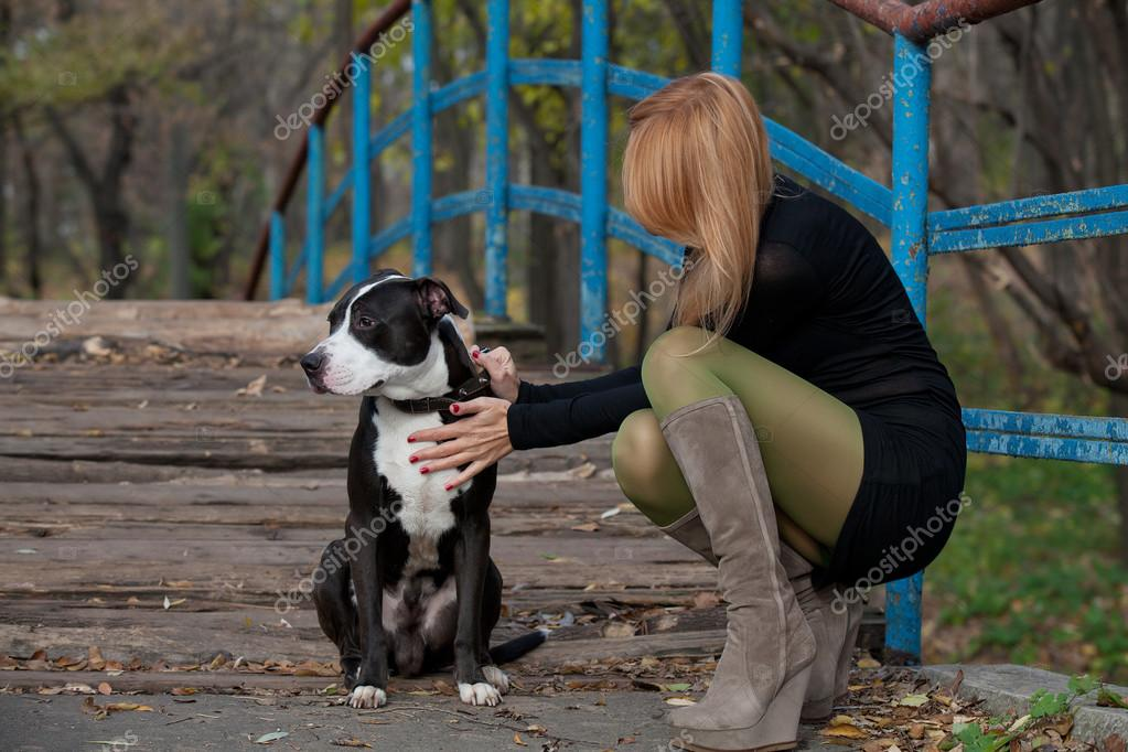 Long-haired blonde woman in high boots stroking dog