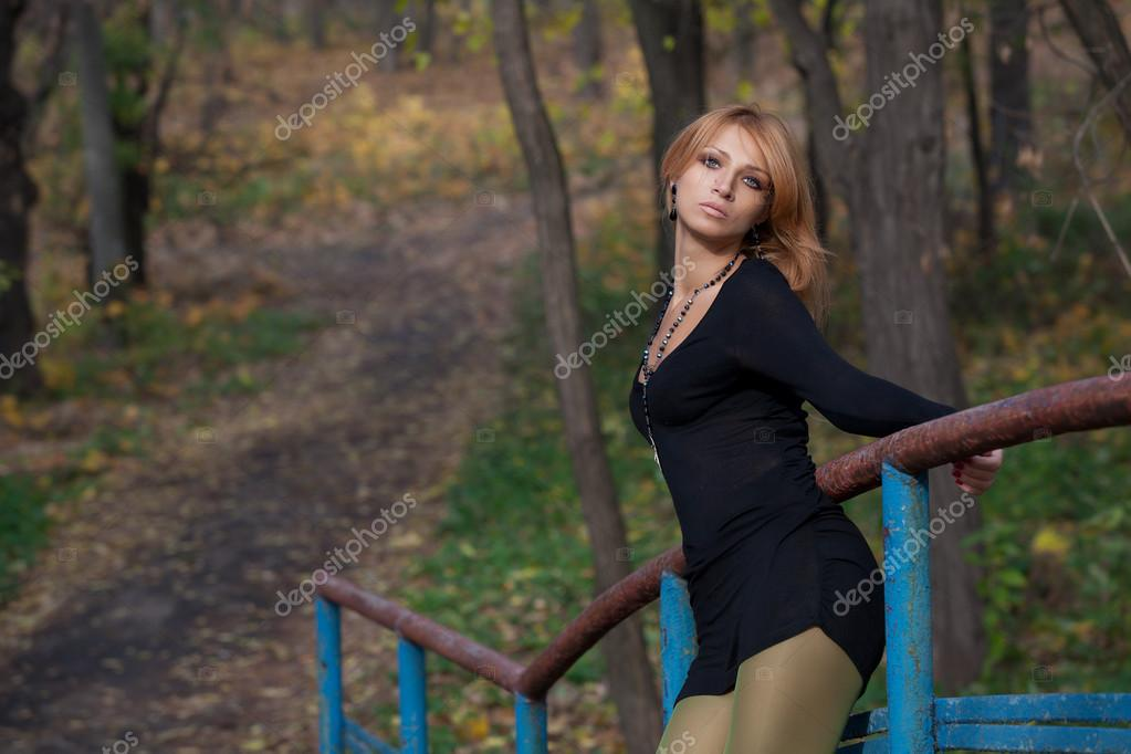 Beautiful blonde woman holds on to the railing footbridge