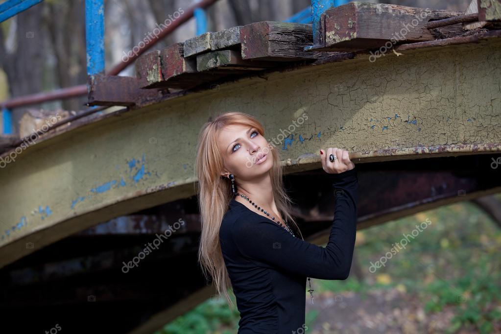 Pretty blonde standing under an old bridge