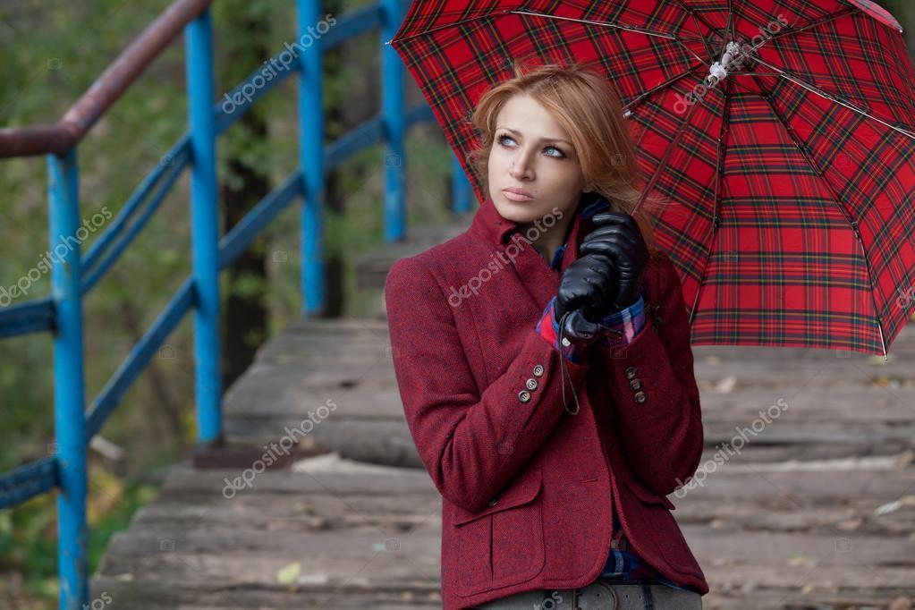 Attractive blonde woman posing under a red umbrella