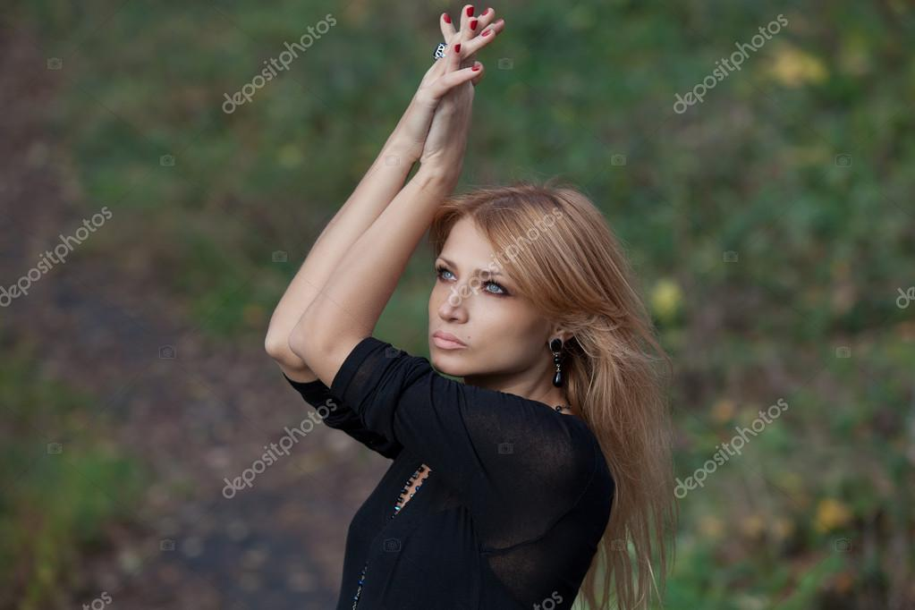 Beautiful mysterious blond woman in autumn forest