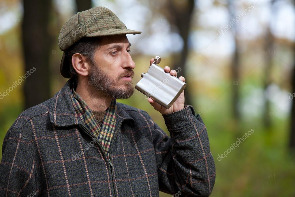 Bearded man brings a flask to his mouth in the autumn forest
