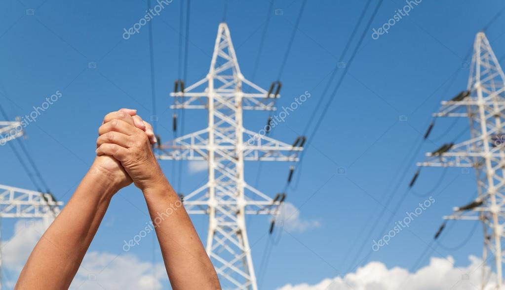 Hands crossed in assent and power transmission lines against blu