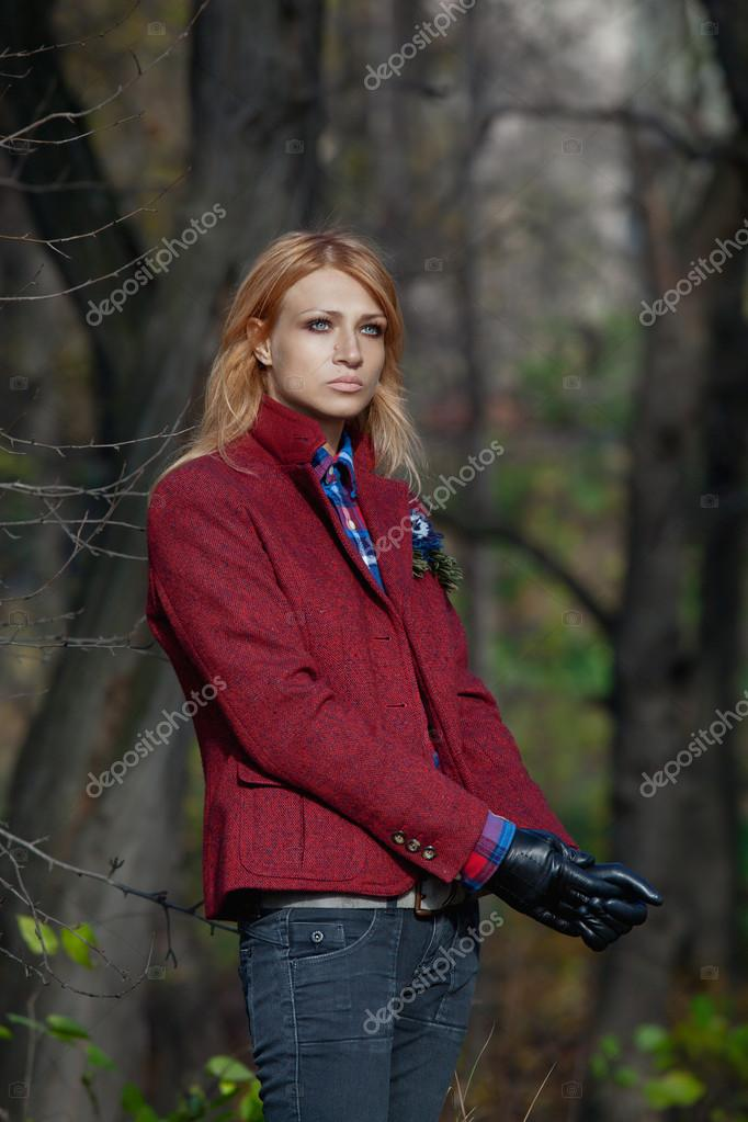 Beautiful blonde woman in tweed jacket and leather gloves in aut
