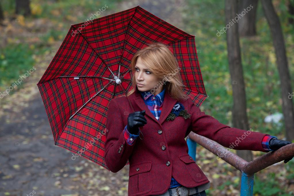 Pretty blonde woman with umbrella in hands posing on the bridge