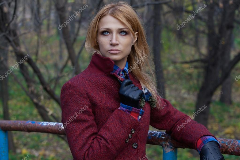 Beautiful blonde woman in jacket and leather gloves in autumn fo