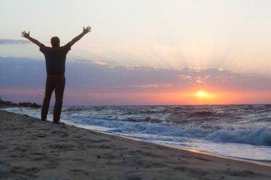 Man welcomes the sunrise on beach