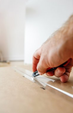 Man opening box with knife