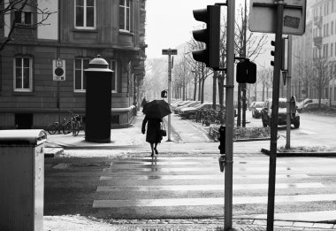 Old woman with umbrella crossing street