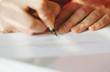 Woman signing contract with fountain pen