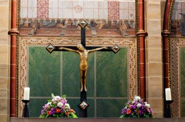 Jesus Christ on cross next to flowers