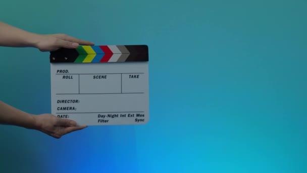 Filmes Szekrény. Egy férfi fogja meg és emelje fel a filmpalát a keretbe, tapsoljon és lépjen ki a keretből. fekete-fehér film palatábla. színes háttér. Videogyártás.