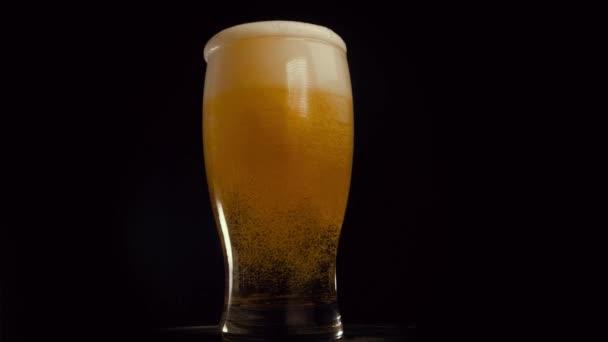 Světlé pivo se sype do skla. IPA. Studené světlé pivo ve sklenici s kapkami vody. Craft Beer tvořící pěnu zblízka. Čerstvost a pěna. Izolované černé pozadí. Mikrobivovarské pivo
