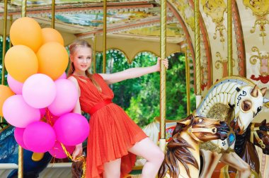 Young model woman riding a carousel