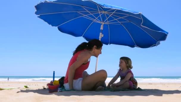 Mutter und Baby spielen blauen Sonnenschirm am Strand herunter