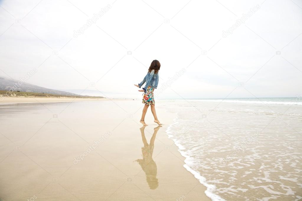 jeans jacket woman touching sea