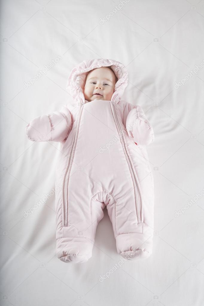 76a24a6ee roze snowsuit baby op bed — Stockfoto © quintanilla  69875473