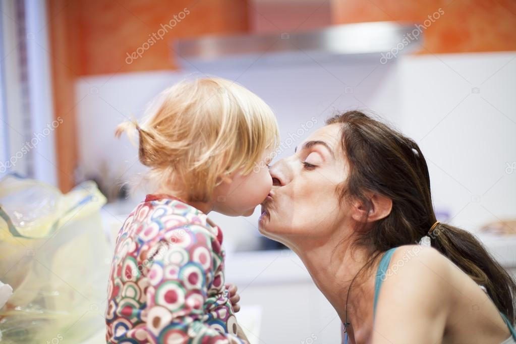 Baby and mom kissing in kitchen