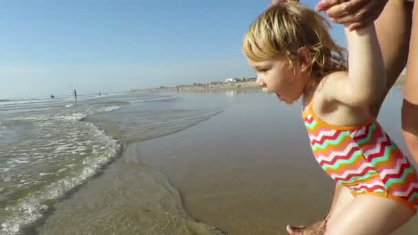 baby walking ocean holding mom hands slow motion
