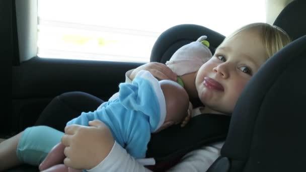 dítě s panenkami v autosedačce